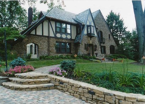 Stone Tudor House pieced stone steps meet brick pavers   front walkway materials
