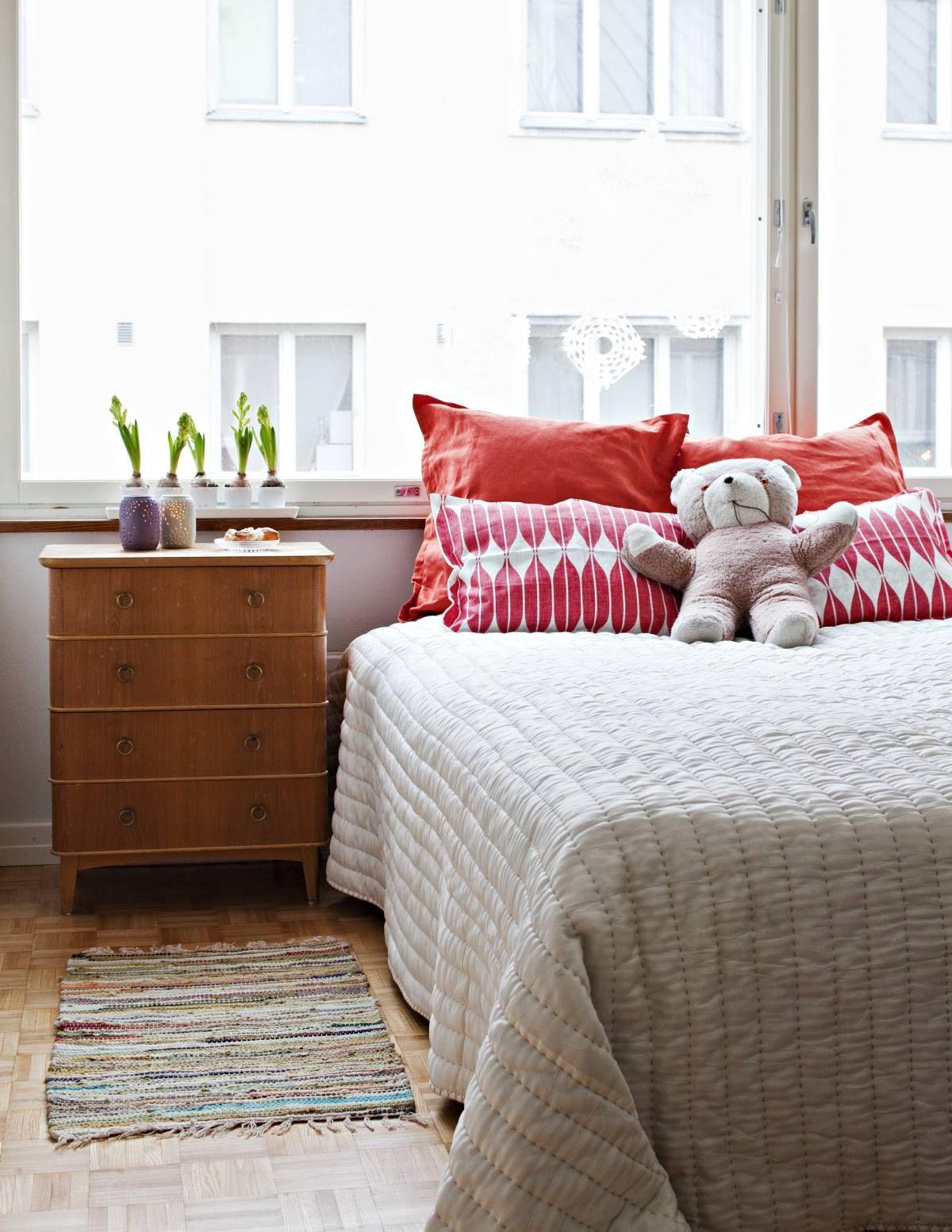 Marjaana hankki makuuhuoneen yöpöydän Iso Roobertinkadun Fida-liikkeestä. Pehmonalle on muisto vauva-ajalta. Pirteät tyynyt on hankittu Mokosta.