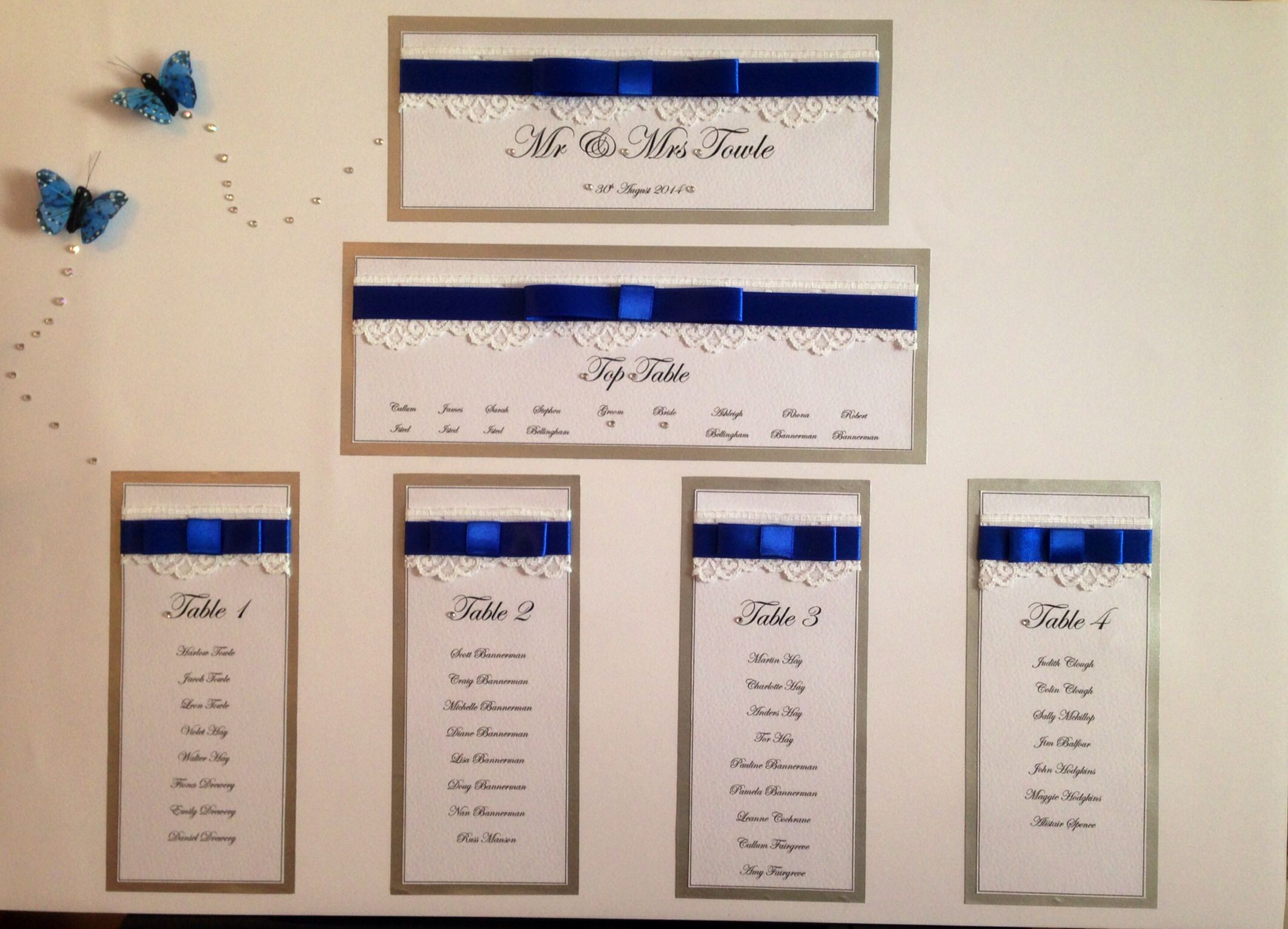 White lace and royal blue ribbon mounted on silver with feather butterfly detail