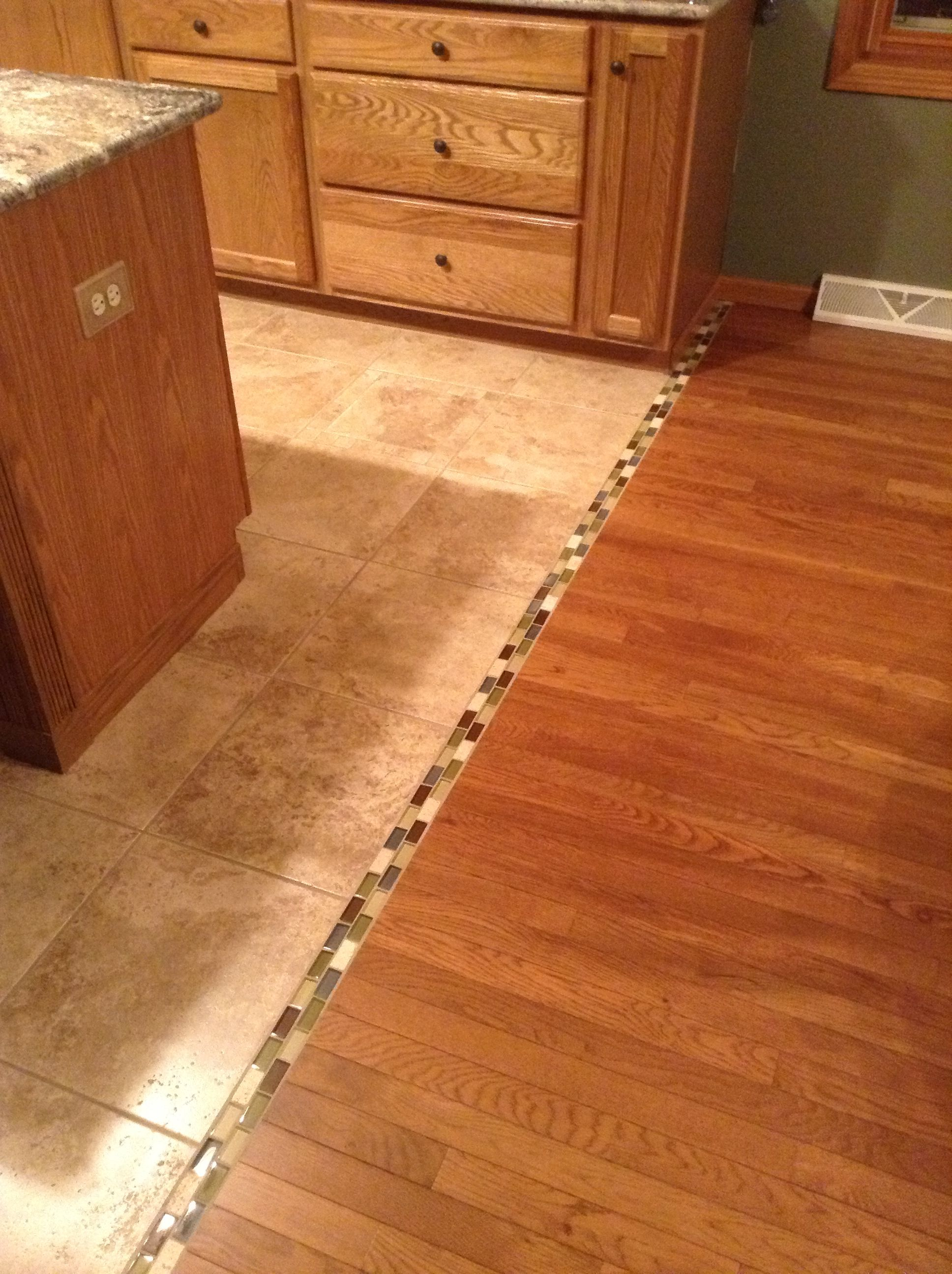 Transition between hardwood and tile floor... We should do this ...