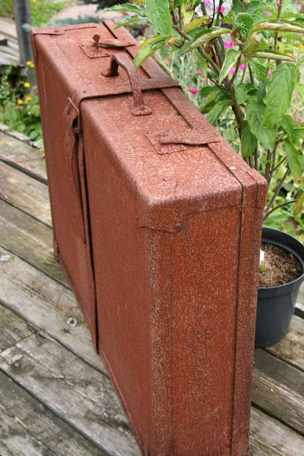 A rusty travel case stands in a garden shop in Porvoo.
