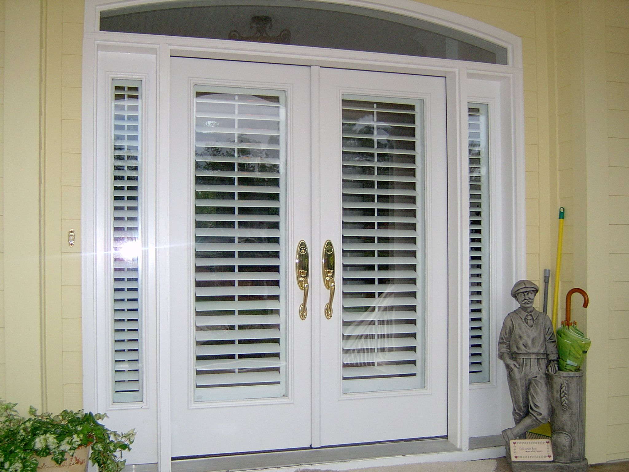 Plantation shutters on a front door exterior view for Entry door with window that opens