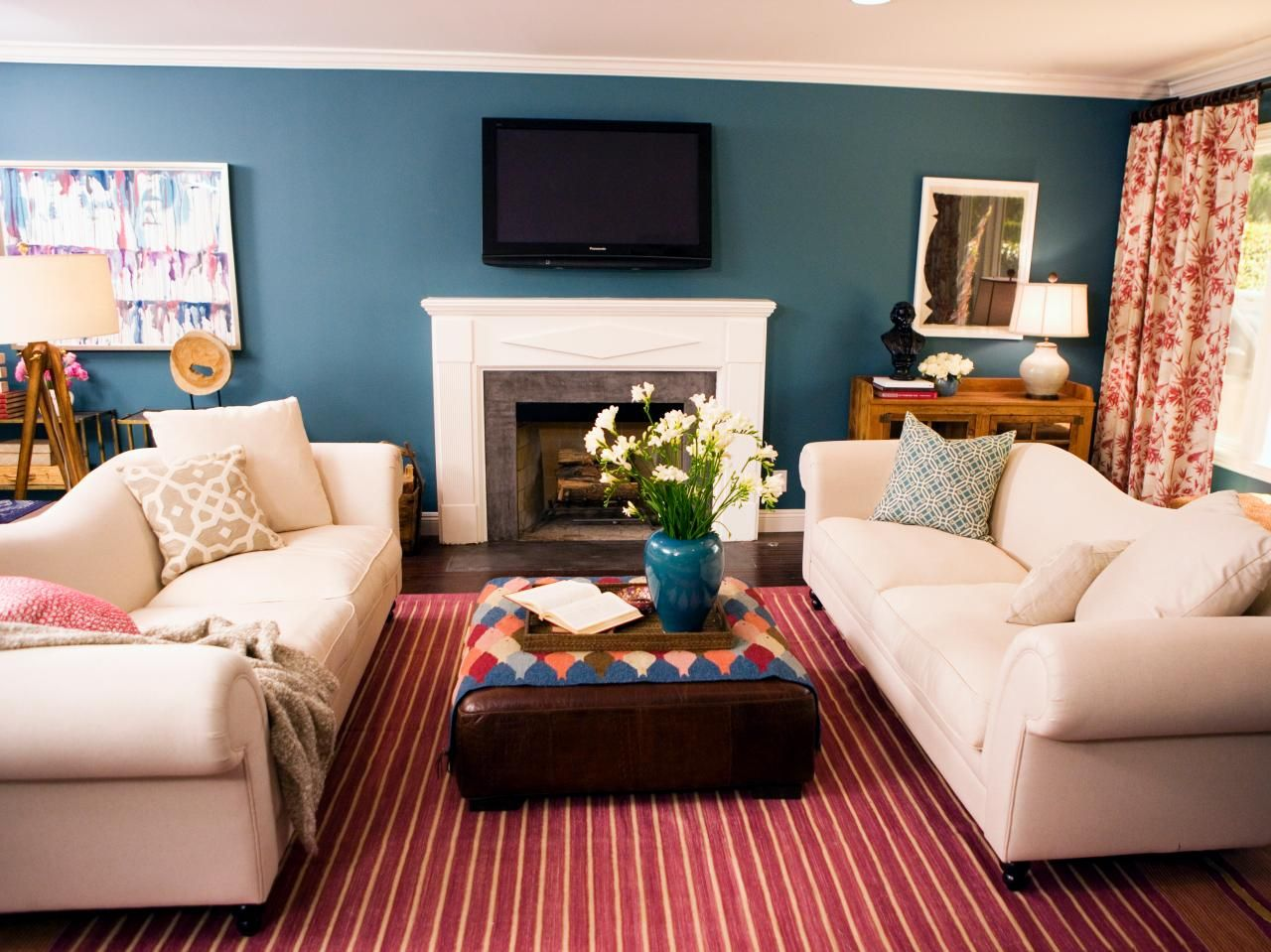 A red striped rug defines this casual living space. White sofas ...