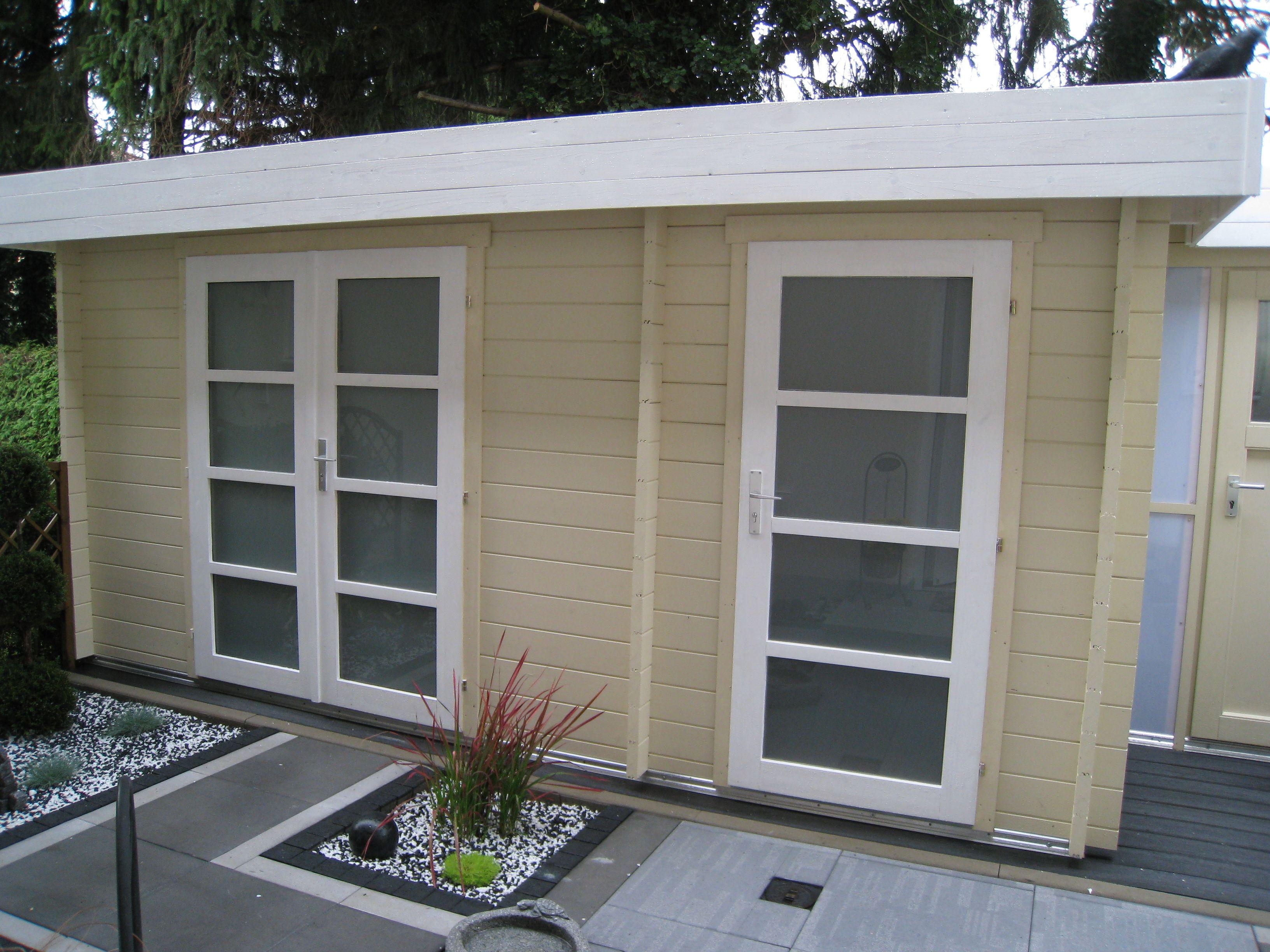 Flachdach Gartenhaus in Vanillegelb, mit modernem Vorplatz