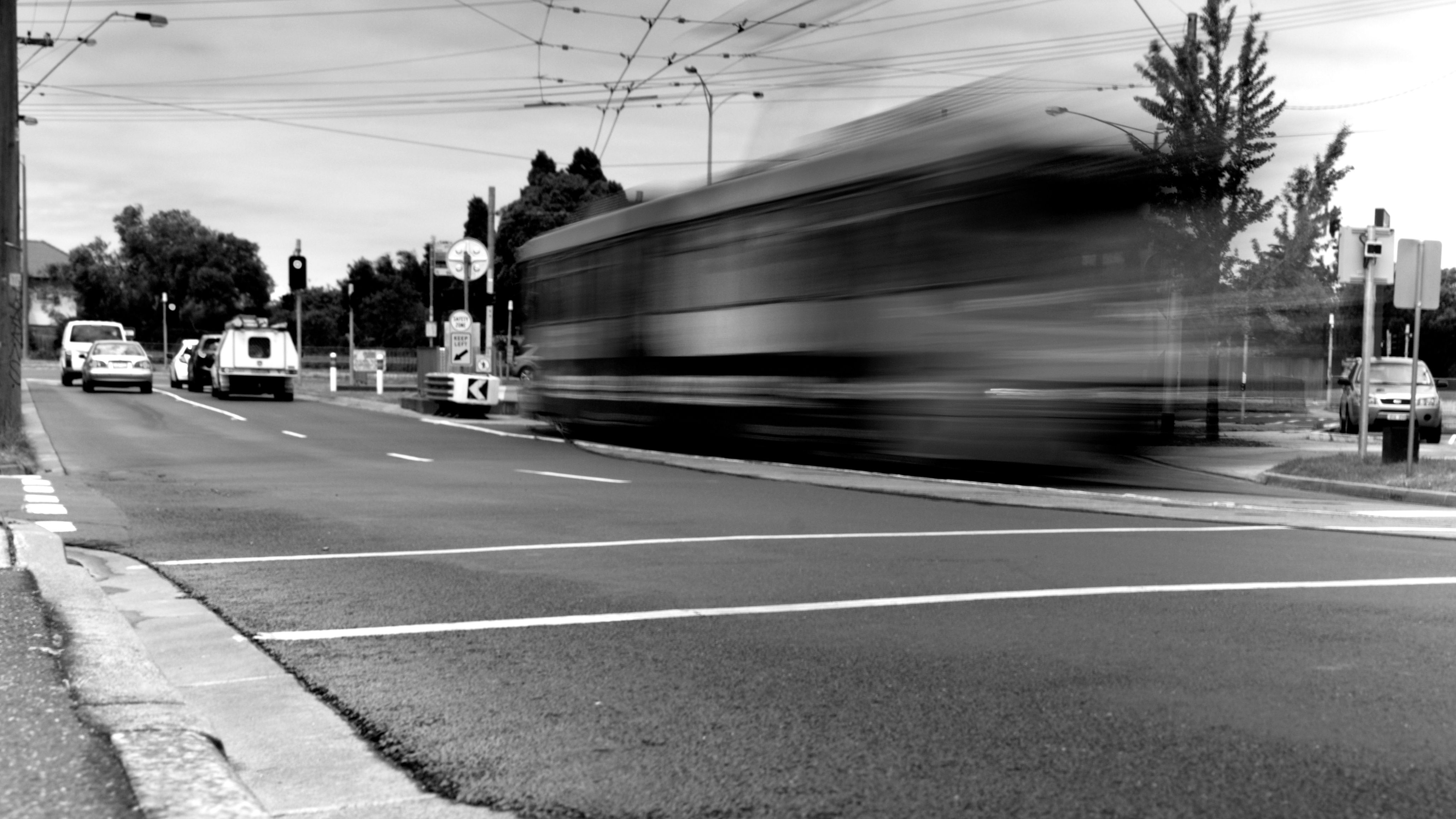 L1M2AS3. Tv Mode. BLURRED MOTION. 1.3 sec, f/8, 45mm, ISO 100. Taken outdoors, tripod, ND filter as it was midday. Long exposure. Focus is on tram. Leading lines above and below the tram - tram cable and road lines- following tram's movement direction.