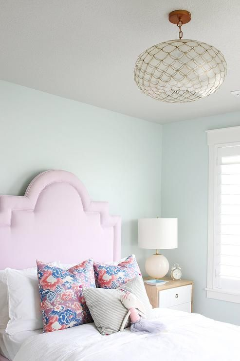 Charming Pink And Blue Girl S Bedroom Features A Serena Lily Capiz Scalloped Chandelier Hung Over Bed Dressed In White Bedding Topped With Purple