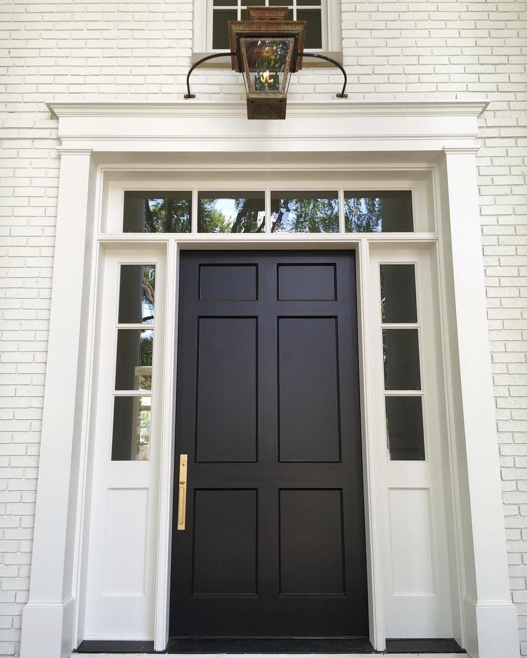 Exterior Design By Jenkins Interiors Black Front Door With Brass Hardware And Gas Lantern Windows Flank Black Exterior Doors Painted Brick House Front Door