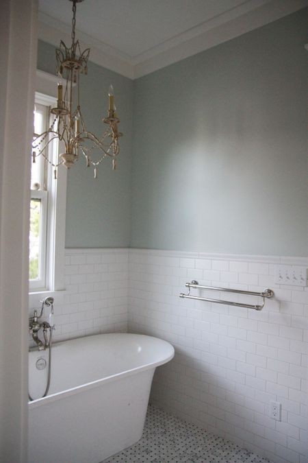 Love everything... the tub, subway tile, that chandelier, the floor tile, natural lighting, and the paint color.