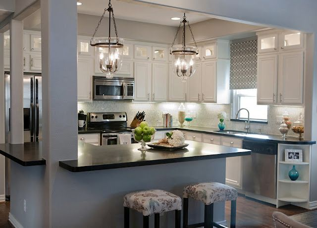 Beautiful open kitchen with extra storage in the lighted upper cabinets and an island to sit at.