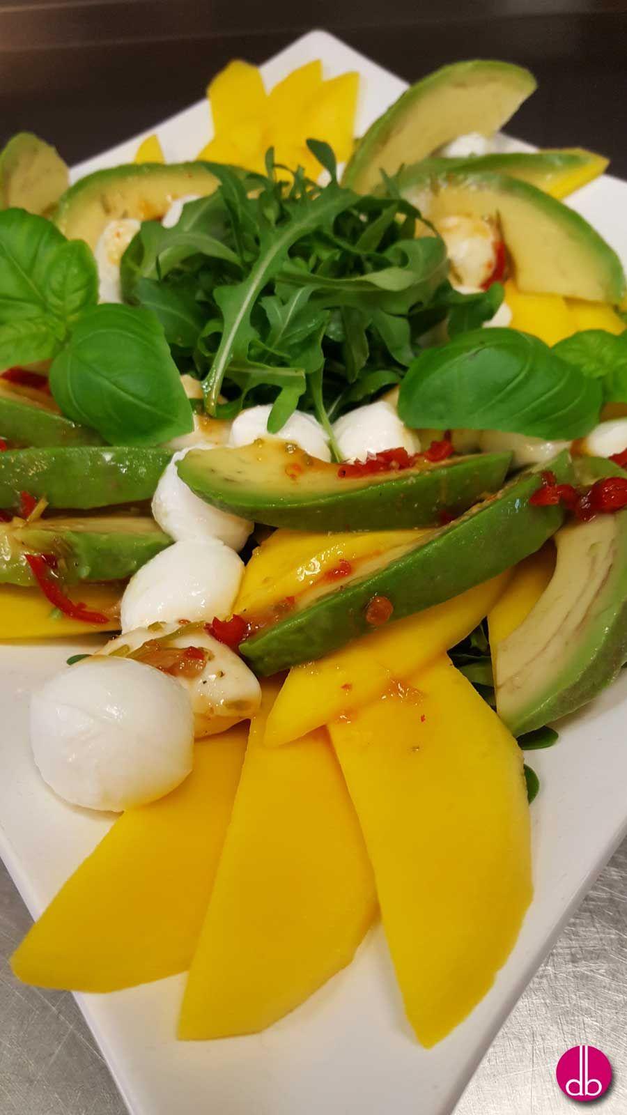 Fruchtige Salatkreation mit würzigem Rucola, Avocado, süßer Mango und oben auf Minis vom Büffel-Mozzarella mit einer Orangen-Honig-Vinaigrette & Chili