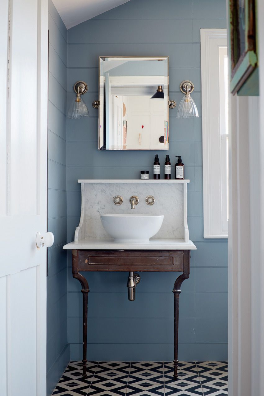 Blue Shiplap Bathroom With Black And White Tiled Floor And Antique