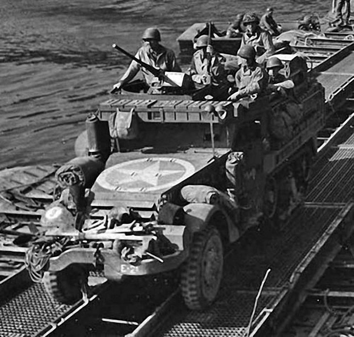 M3A1 half-track of the 36th Armored Infantry crossing the Seine River in France directly behind tanks of the 3AD on August 26, 1944. Note the use of a shelf above the armoured windshield to store .50 cal ammo boxes.