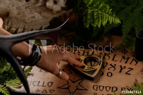 Photo of Mystic ritual with Ouija and candles. Devil's board concept, black magic or fortune telling rite with occult and esoteric symbols.