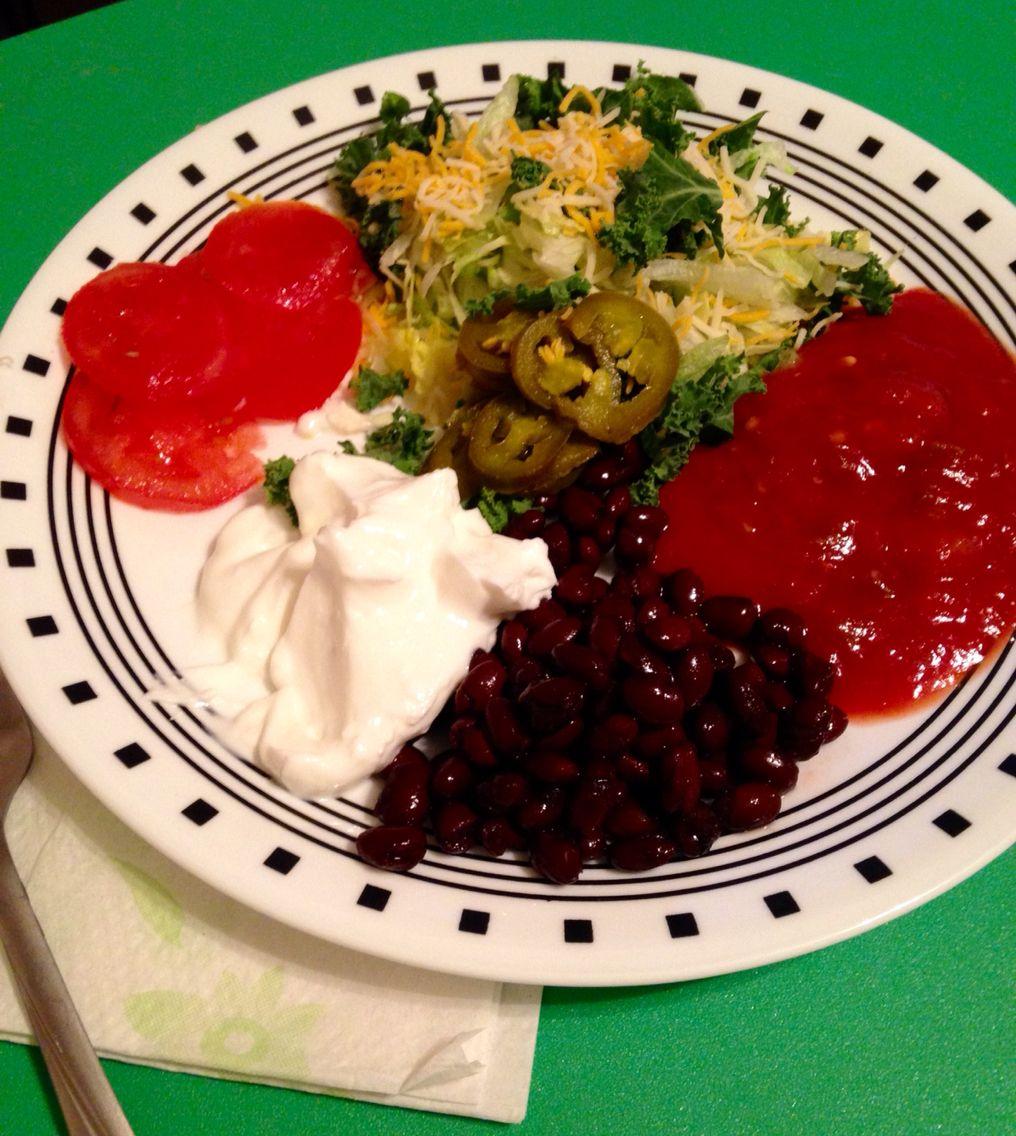 Vegetarian nachos.  Ingredients: Black beans  Kale/ Lettuce Roma tomatoes  Plain Greek yogurt Jalapeños  Cheese and Salsa