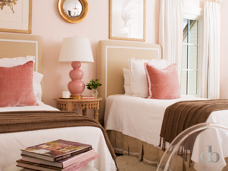Pink and tan bedroom features a pink wall lined with framed