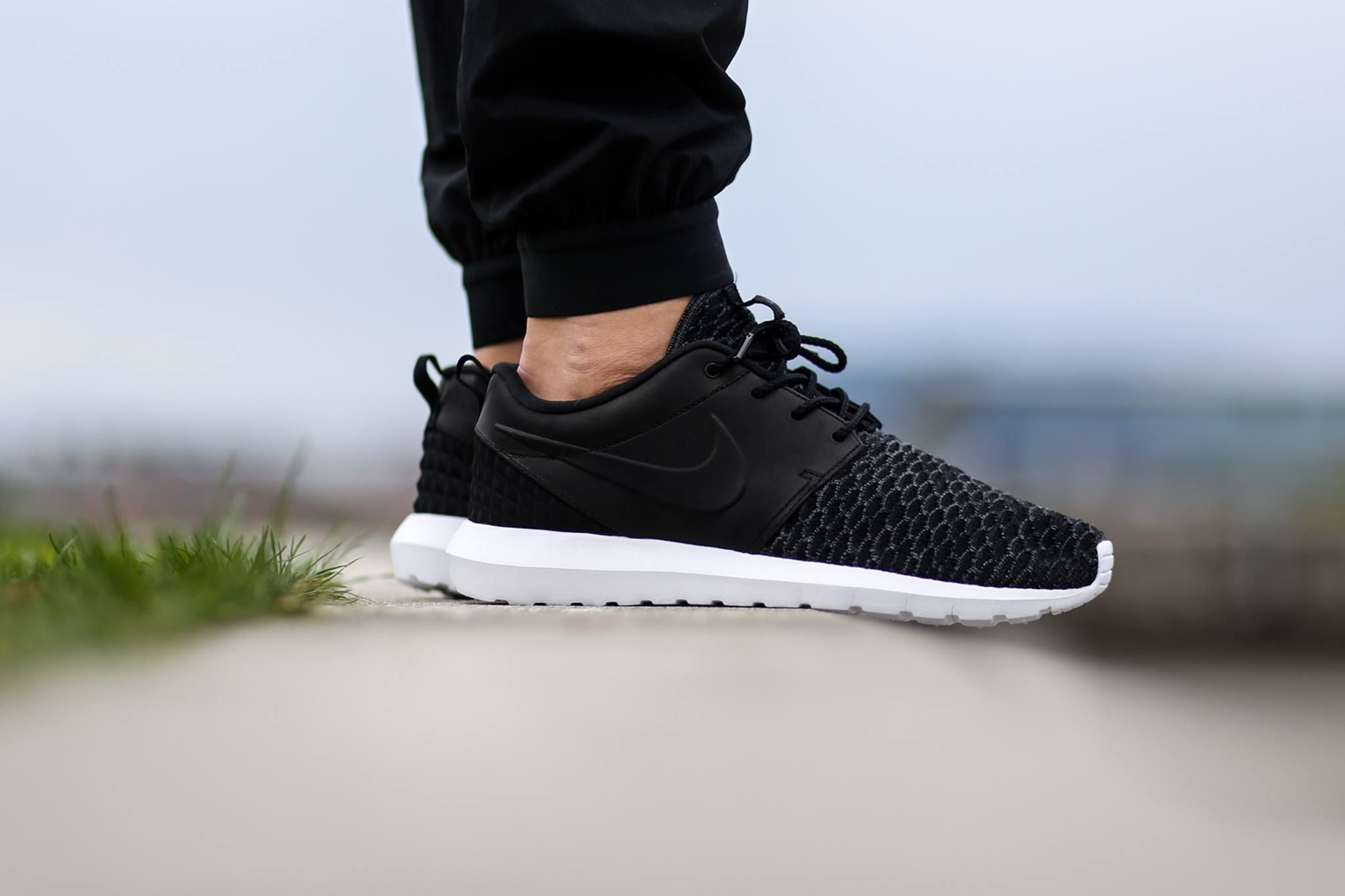 A clean black colorway of the Roshe One has been given the premium  treatment by Nike Sportswear. Built atop the silhouette's signature white  sole unit, ...