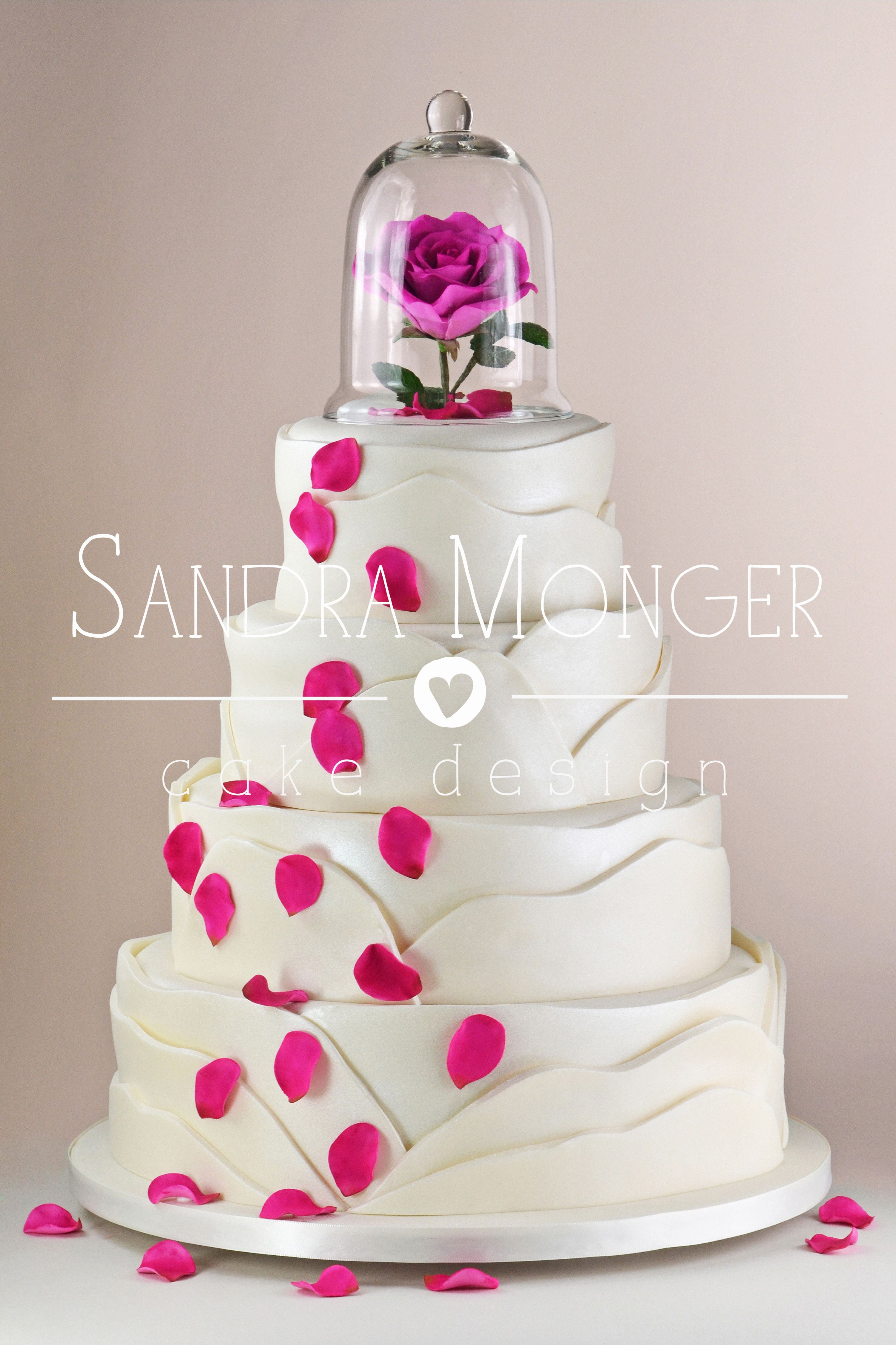 Beauty and The Beast inspired wedding cake with pink petals and a ...