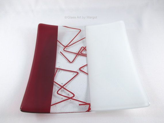 One of a kind square plate. I made this fused glass piece by bending thin spaghetti like pieces of glass, called stringer, in a flame and fusing it to clear glass. I then combined it with transparent red glass and white glass. The white glass has a subtle sandblasted design element that mimics the stringer (see the last picture). The clear glass has champagne bubble adding interest to the piece. Use this plate to serve cookies, canapes, and more. This would make a lovely addition to your…