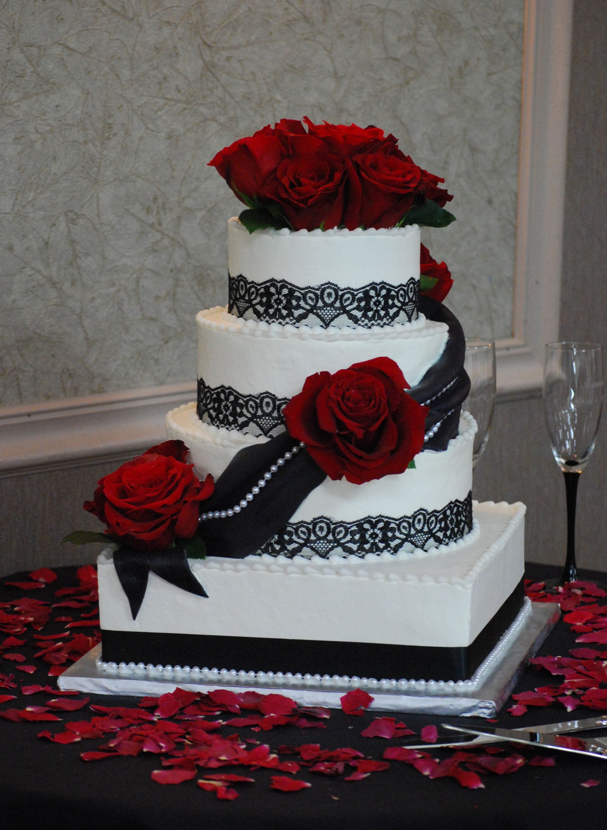 square and round wedding cake with black lace borders dark red roses and black fondant
