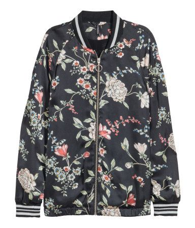 Black floral. Jacket in satin with a printed pattern. Zip at front, elasticized hem, and ribbing at neckline and cuffs. Chiffon lining.