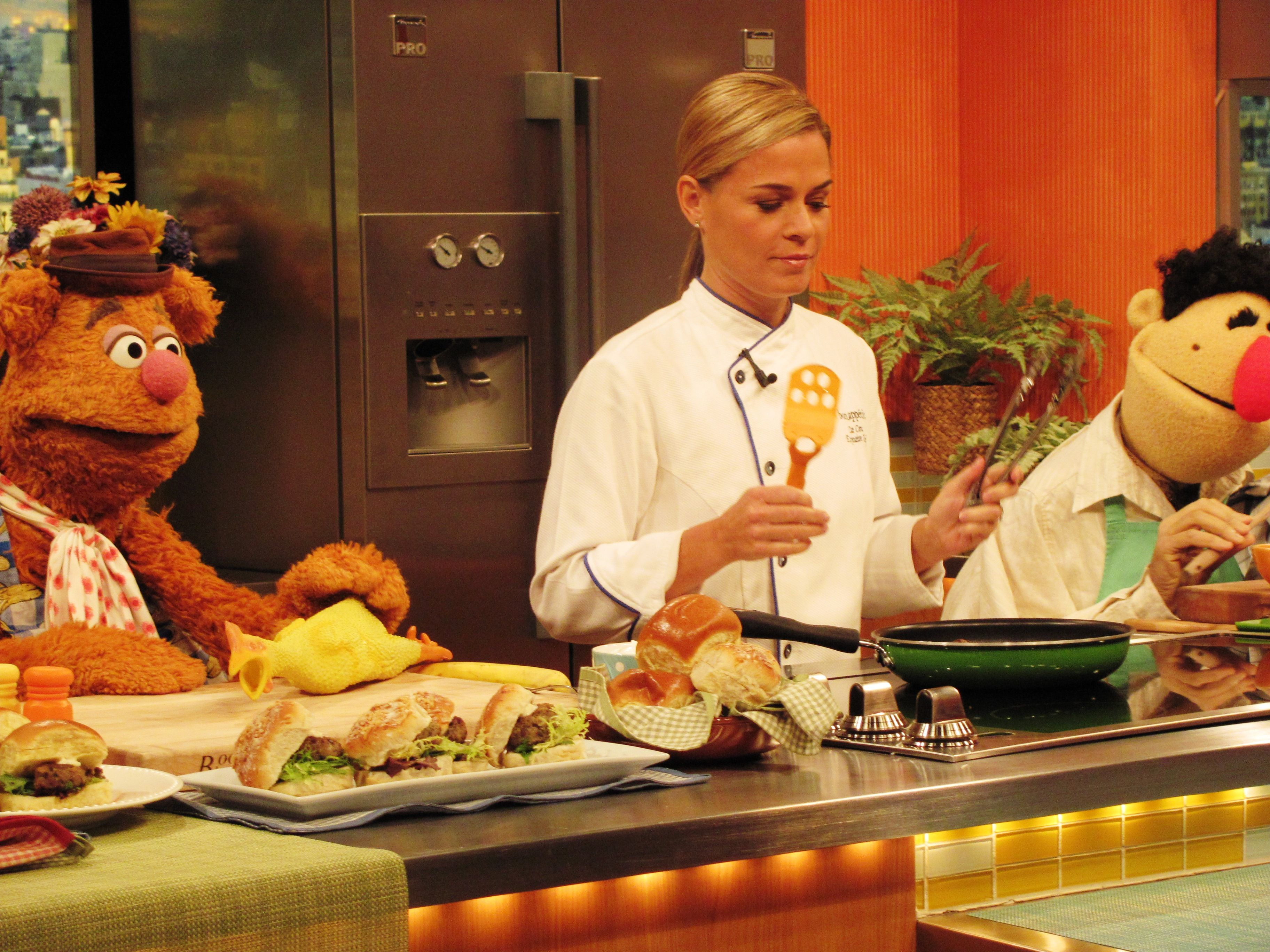 Cat Cora and the muppets standing by