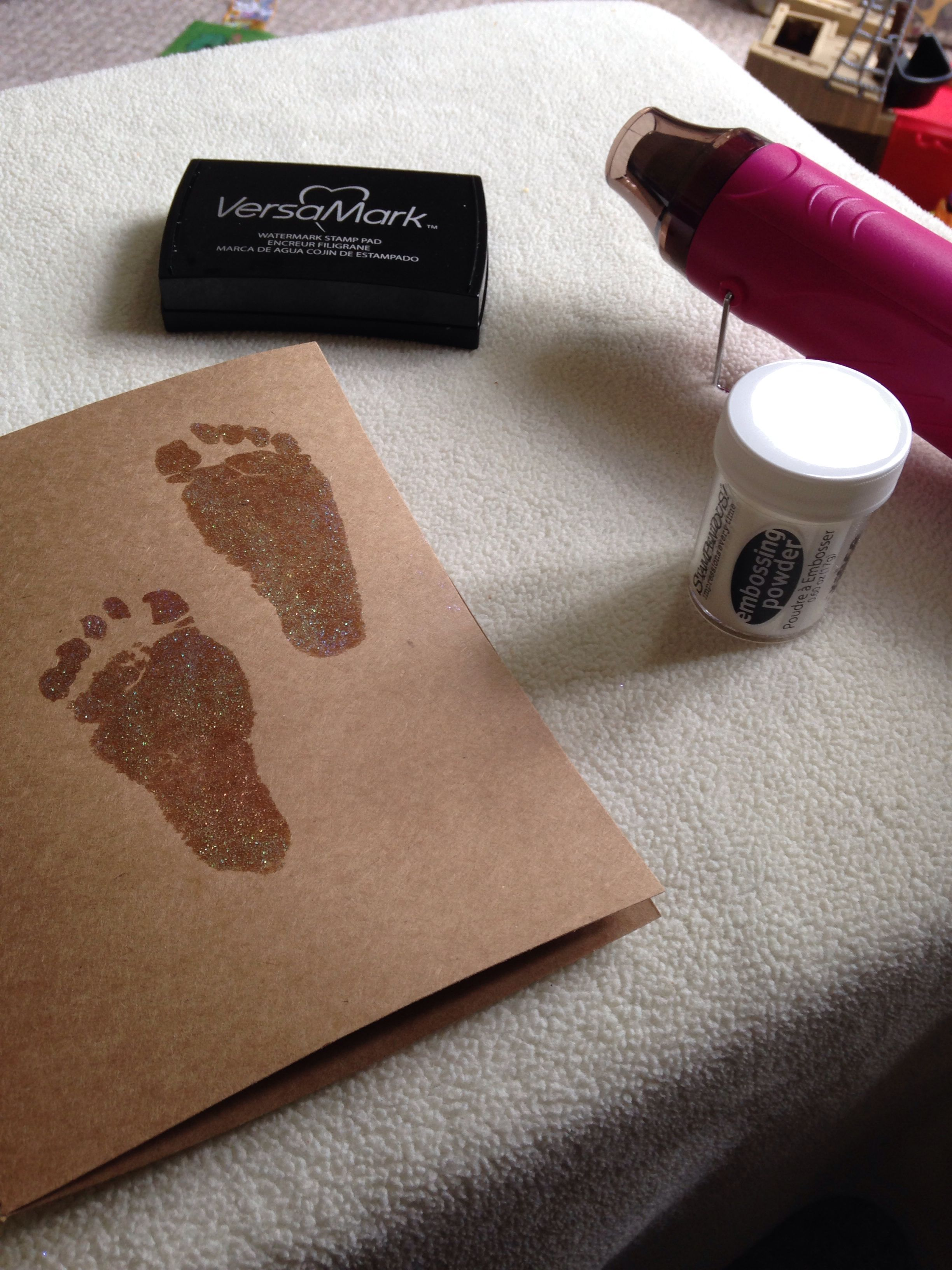 Capturing my baby girls footprints using versamark and embossing powder. Doesn't stain her feet and is easy to clean off unlike normal paints.