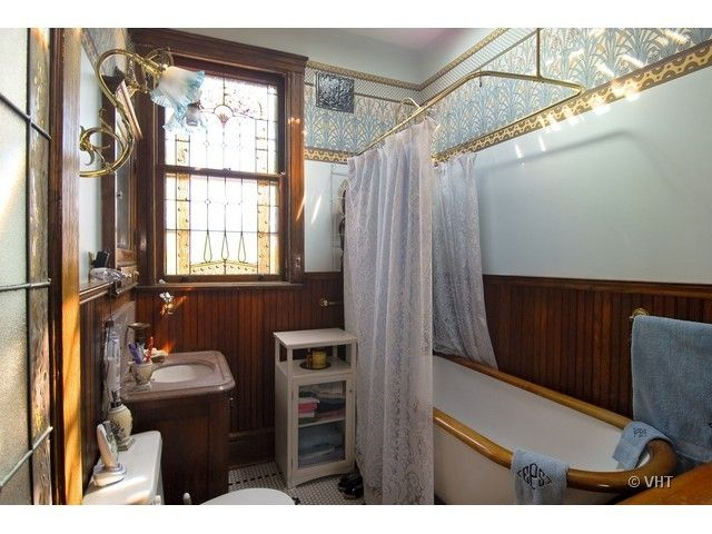Bradbury wallpaper and stained glass make this Victorian bathroom