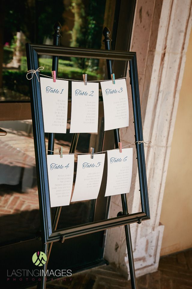 Empty wooden frame with seating chart cards attached to clothesline ...