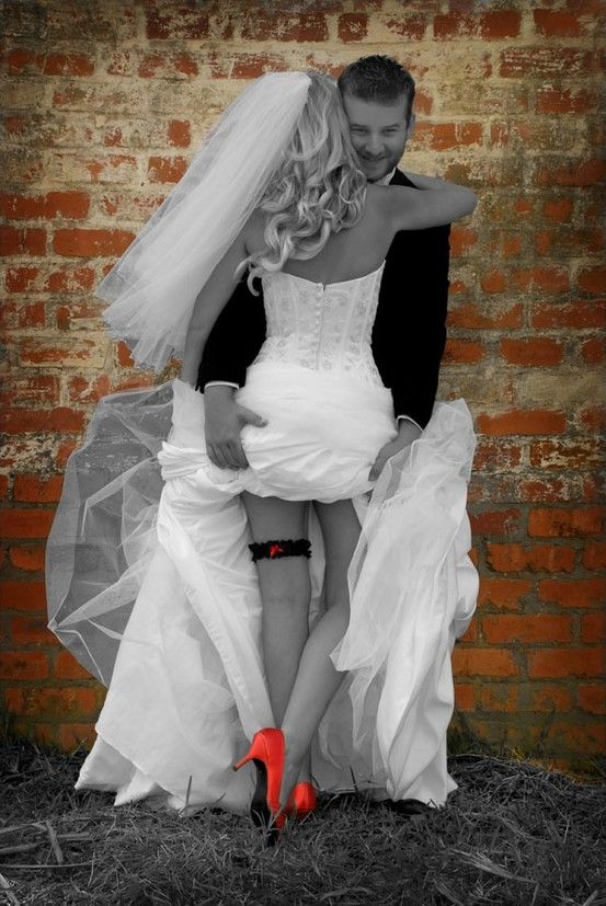 I love how the bride and groom are in black and white and there is a pop of color in the shoes, garter and brick wall!