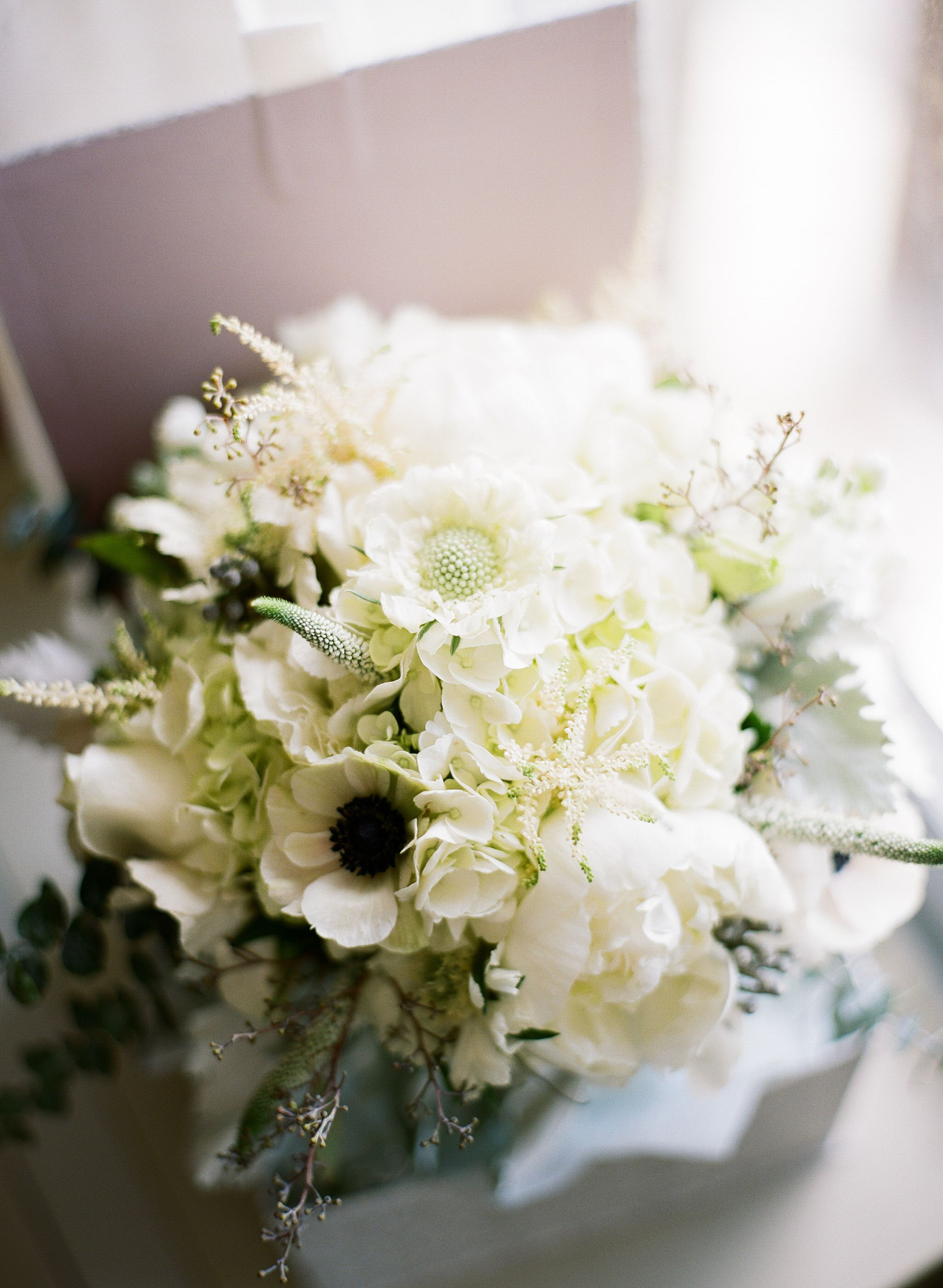 Elegant bridal bouquet of white hydrangea, white peonies, white sterling, white anenomes, dusty miller and 2 different eucalyptus in a beautiful box you get to keep! Photo by: Taylor DiVincenzo Photography #bridal #elegant #white #peonies #dustymiller #bouquet