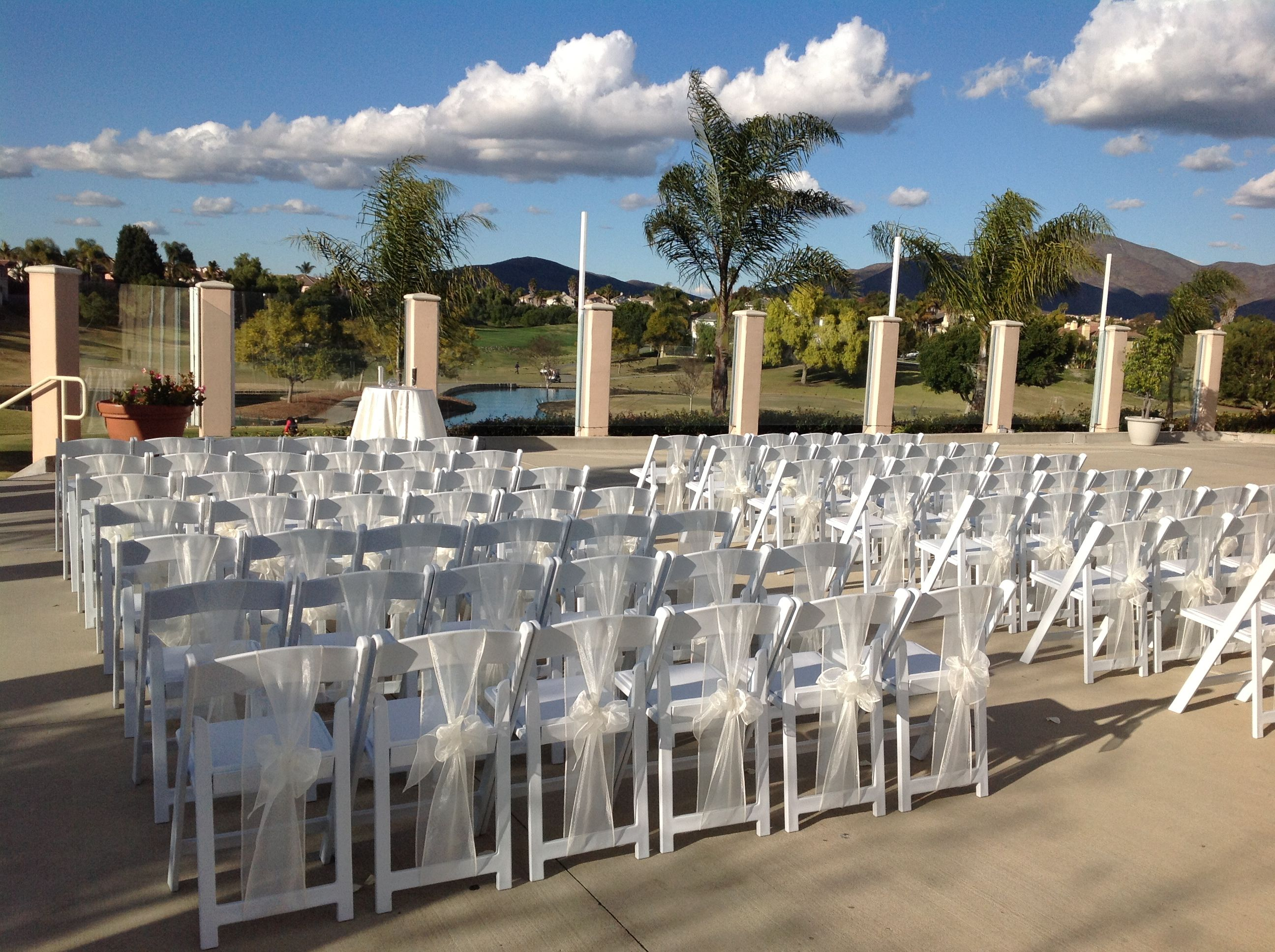 Ceremony Set Up Of White Resin Folding Chairs With A Padded Seat And An Ivory Sash Tied In A Bow To Give A Clas Wedding Chairs Wedding Decorations Chair Sashes