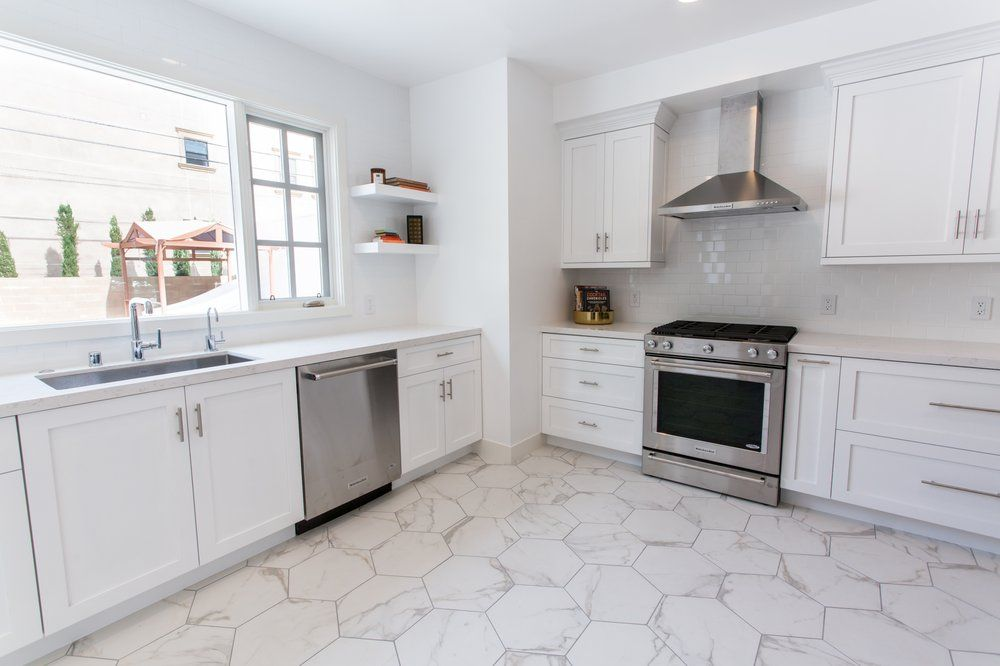 Beautiful Clean White Kitchen With Carrara Marble Countertops And