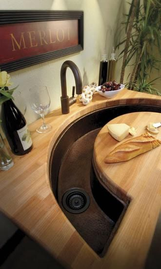 kitchen sink with cutting board in front of it.
