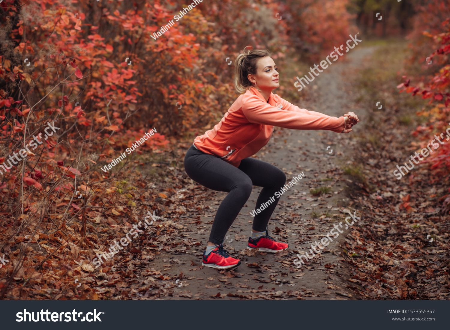 Young attractive sport woman in sportswear doing squats exercise in autumn forest with reddened lea