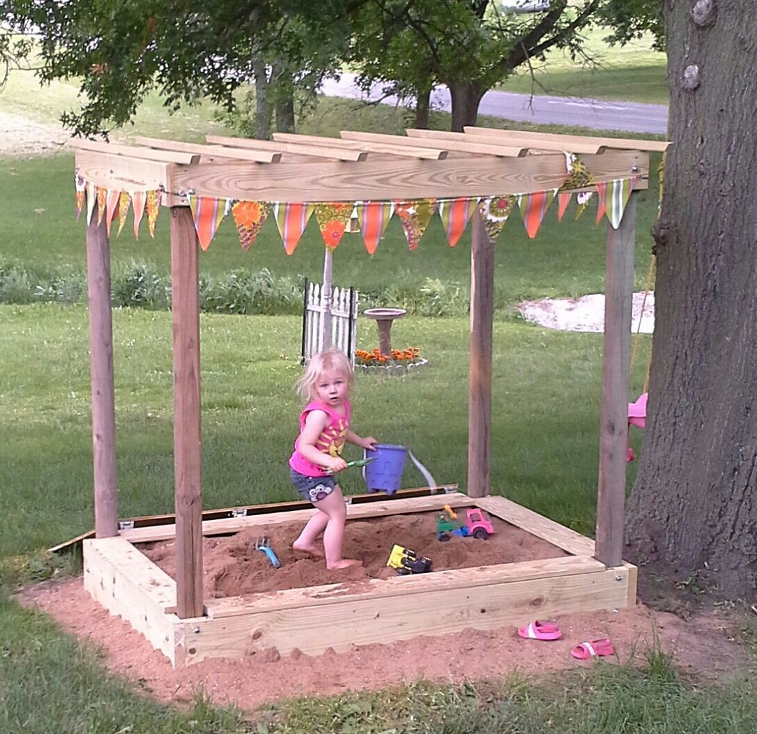 Sandbox with pergola roof and flag banner also has an attached