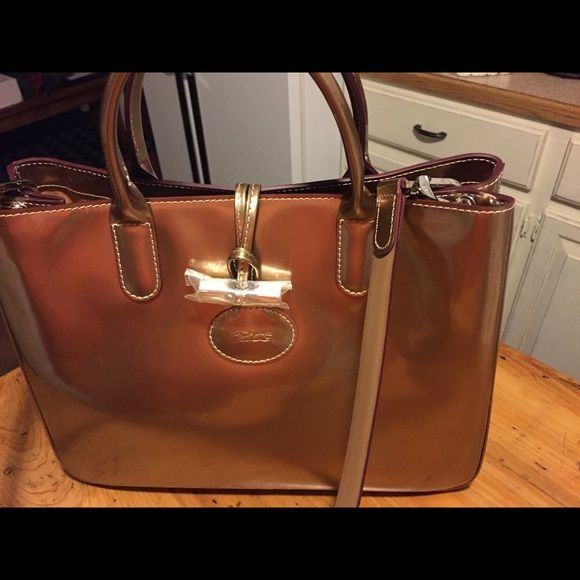 Longchamp Bag You know the quality of a Longchamp!  This Elegant Brand New Metallica  Bronze Longchamp beauty is priced to sell. NWOT! A true beauty in every respect. Longchamp Bags