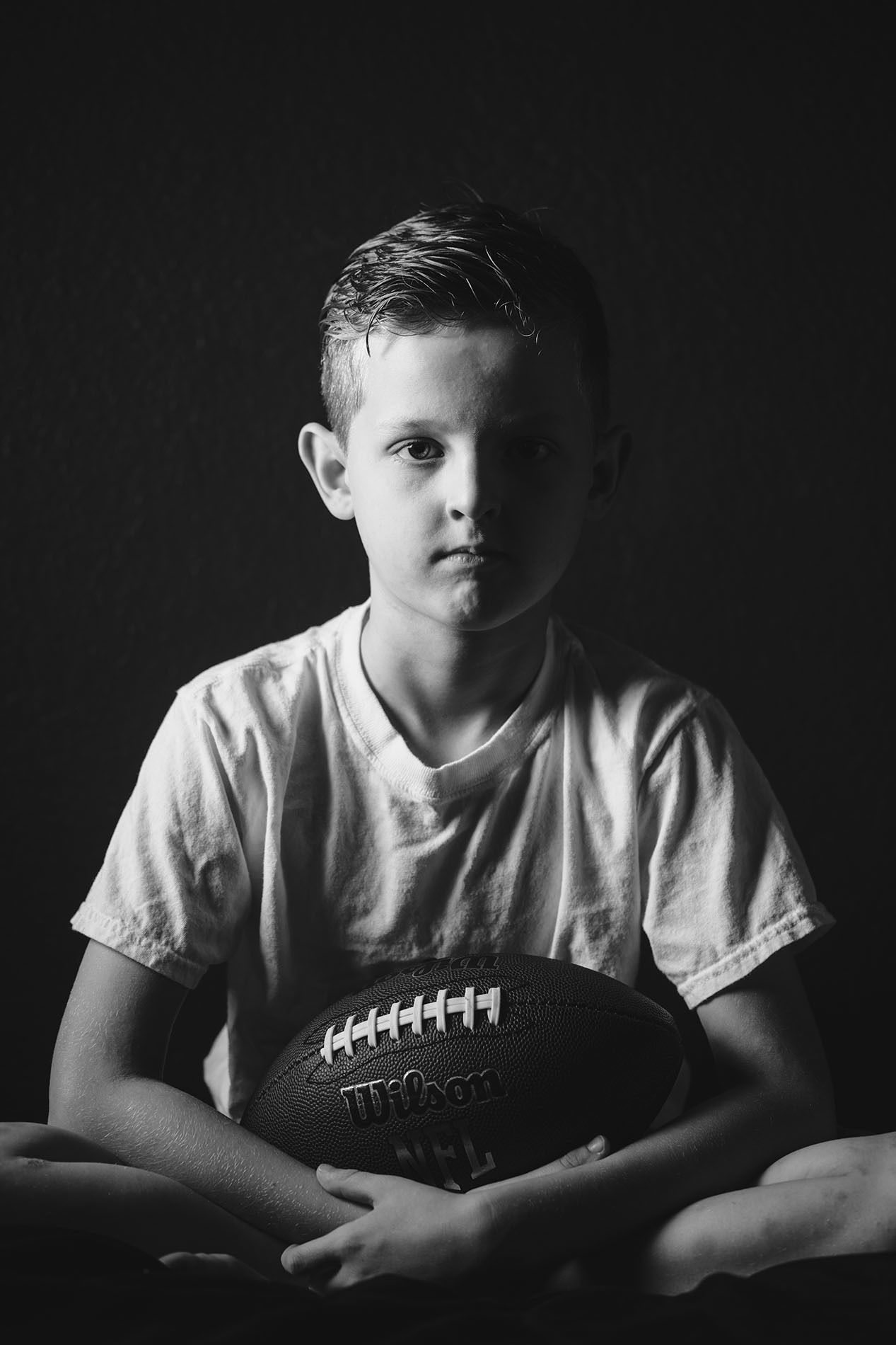 When and how to use these 8 types of photography lighting split light black and white photo of boy holding a football by april nienhuis