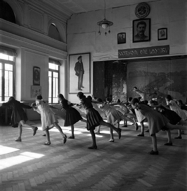 """Morning exercise in a girl's classroom. The sign below the portrait of Stalin reads """"gaumarjos did stalins!"""" (Cheers to the great Stalin)"""