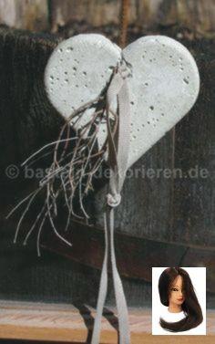 Herz aus Beton mit einem Satinband und einem kleinen Ästchen dekoriert
