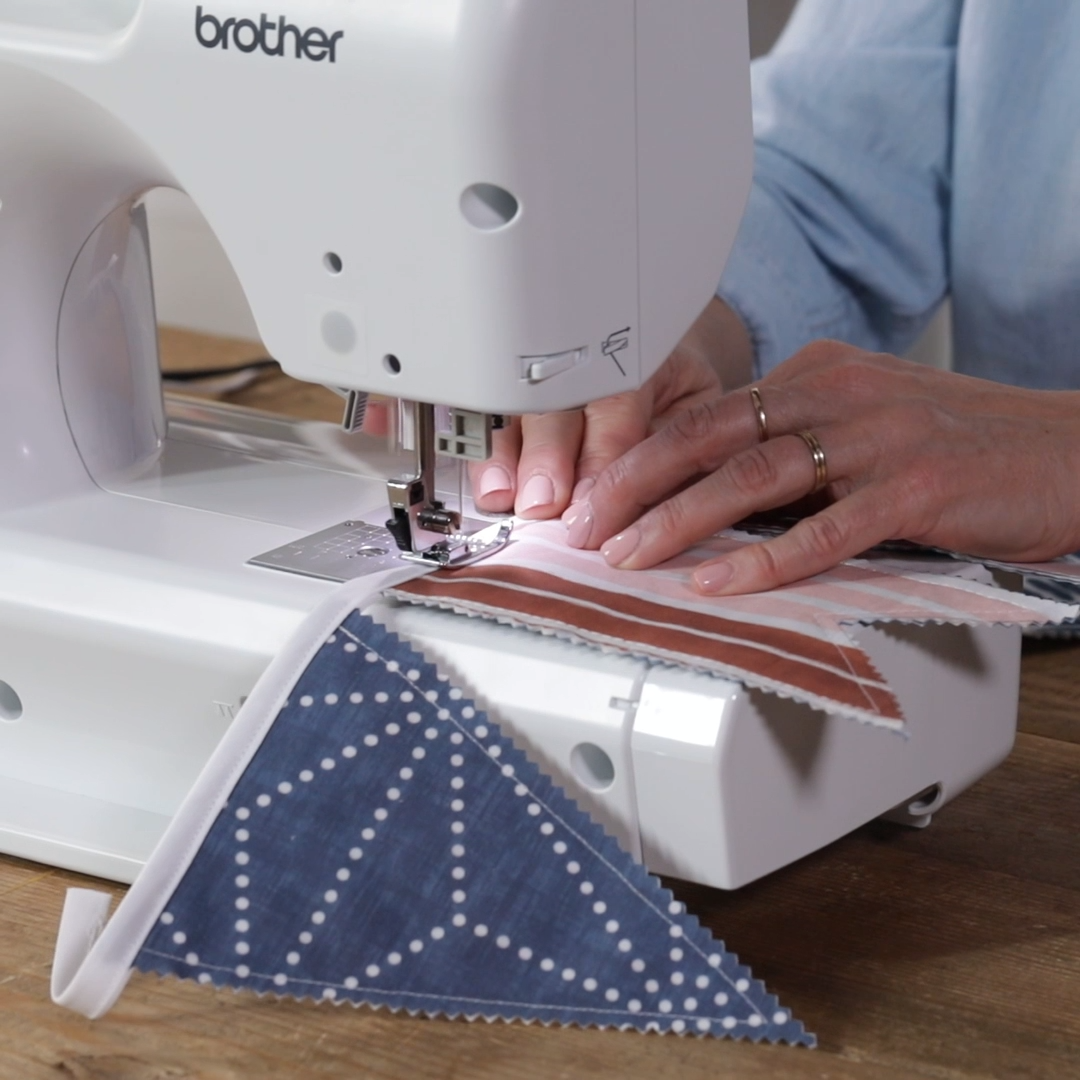 We'll show you how to make a fabric bunting garland in five easy steps. It requires only basic sewing skills, and it's so inexpensive. #fabricbunting #diy #bunting #banner #decor #garland #howtomake #bhg