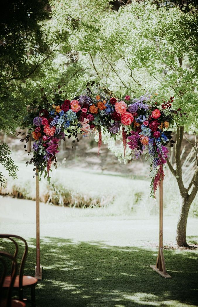 7 Wedding Arches That Will Instantly Upgrade Your Ceremony - Colorful flowers decorated wedding arch - Fall wedding ideas #fallwedding #autumnwedding