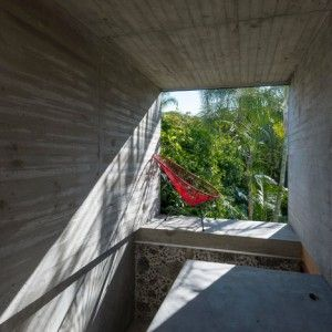 Concrete tunnel extends through an old  stone wall at Leyva 506 house by APT  - Love the ideas. The execution? Not so fabulous. I picture concrete tunnels as dark and intimate, smooth and not needing direction for you to know where to go. This seems more like a covered balcony.