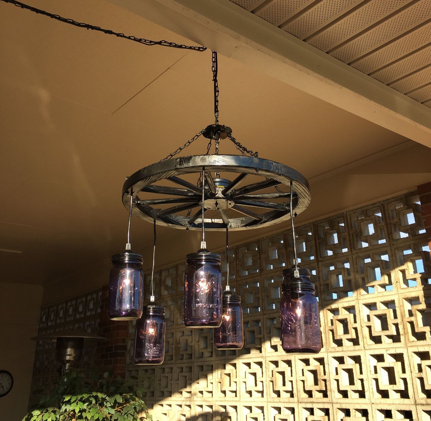 Wagon wheel chandelier by southerncharmbykaren on etsy chandeliers wagon wheel with 6 mason jars wheel is white in color and it comes with 6 pint and clear mason jars aloadofball Gallery