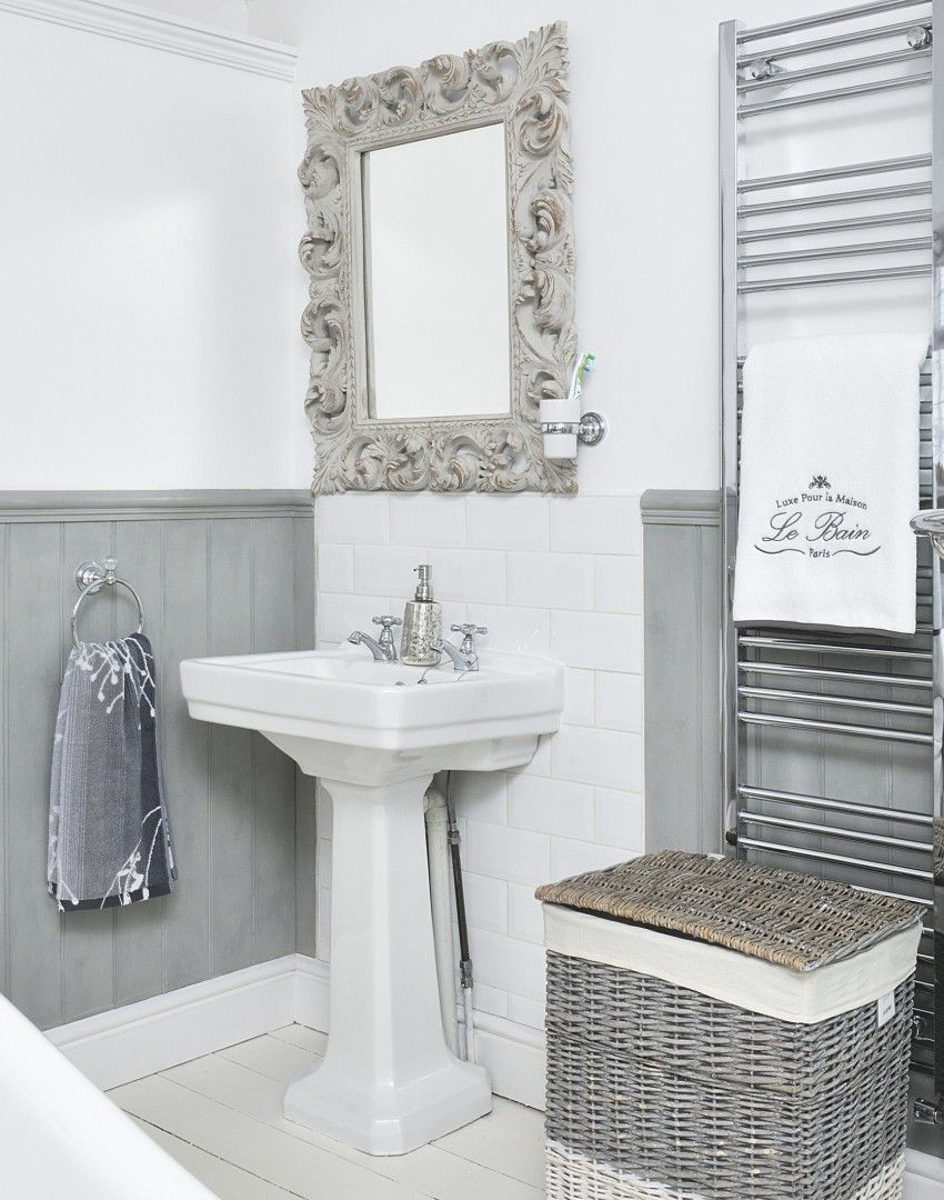white and grey boutique hotel-style bathroom with ornate mirror