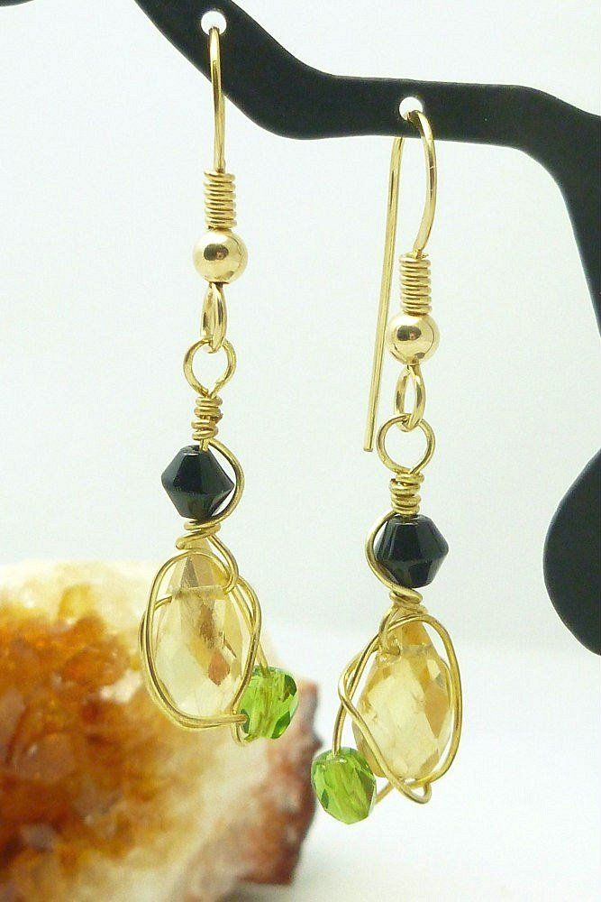 Yellow golden citrine faceted briolette gemstones accented with a 4mm Czech fire polished olive green colored crystal, and black bicone glass bead. Co