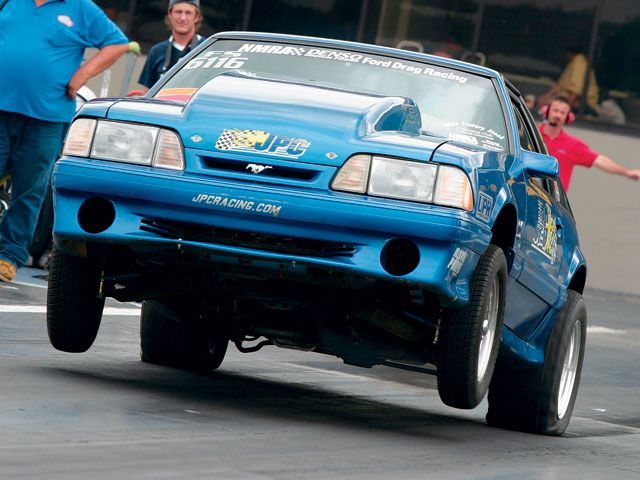 Blue Ford Mustang Foxbody GT doing a wheelie at drag strip