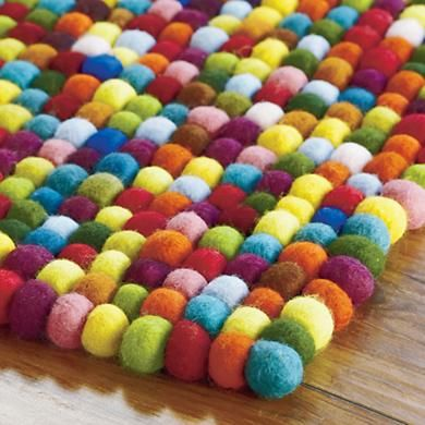 I seriously want one of these!!!  If I knew how to felt then I could make 1000 of my own pompoms and then sew them into a rug! LOL!