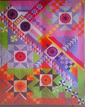 """...quilt that I call ""Lazy Dazee Joins the Circus"". It was a mystery project in American Quilter magazine in 2011 that called for 7 focus blocks plus 12 other fabrics. All the fabrics except the light pink and dark purple came from my stash -- the only reason I bought those was that I didn't have any pieces large enough that worked with the color palette. Susan Greene Danville, CA"""