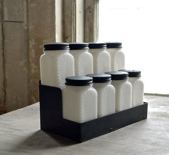 Vintage sun ray milk glass spice jar set. Set of eight white jars with black metal lids and rack. Jars have the sun ray design on two sides and are