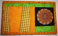 Design is a woven Sunflower bursting out with orange, yellow and green fabrics!     WACKY...YES  WONKY...DEFINITELY  UNIQUE...TOTALLY  If something doesn't look right or not straight...it was made that way just for YOU!  One of a kind mini quilt that in...